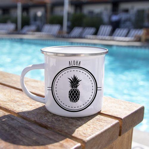 En bord de piscine, un mug en métal émaillé avec un ananas