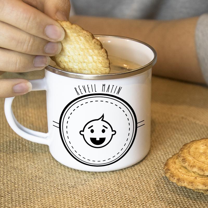 Une main tremps un biscuit dans un mug en métal émaillé avec un bébé