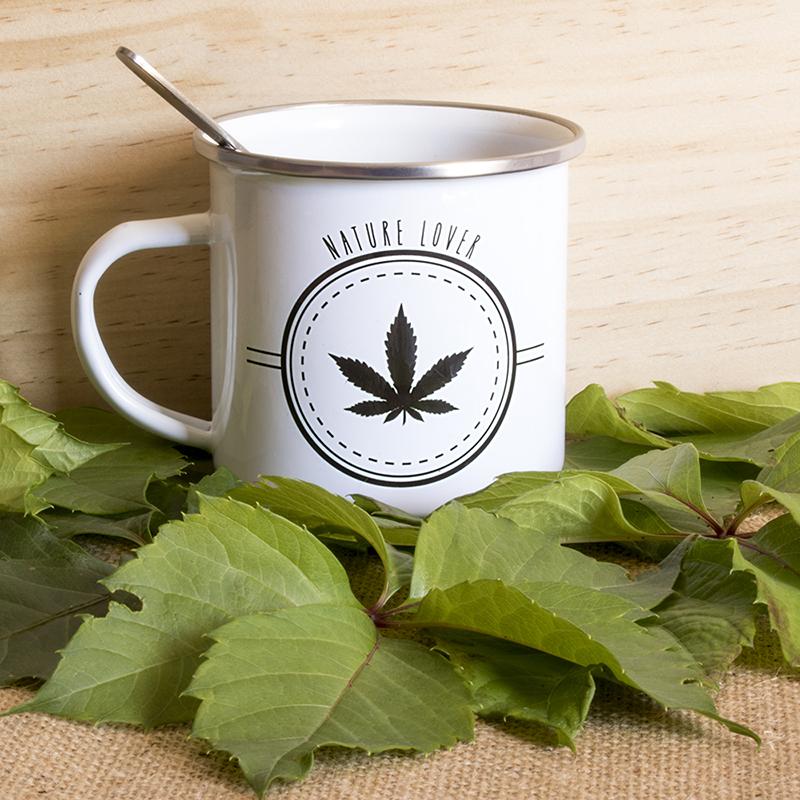 Du thé dans un mug émaillé avec une feuille de chanvre