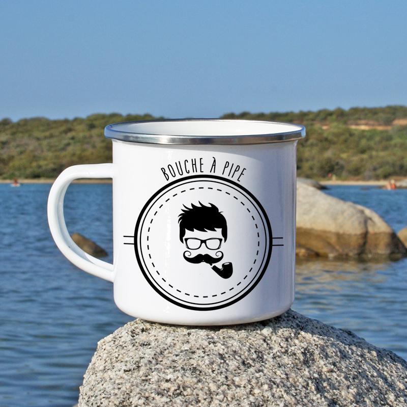 En bord de mer, un mug en métal émaillé avec un fumeur de pipa