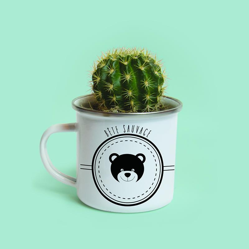 Mug en métal émaillé avec un petit ours, servant de cache pot pour un cactus
