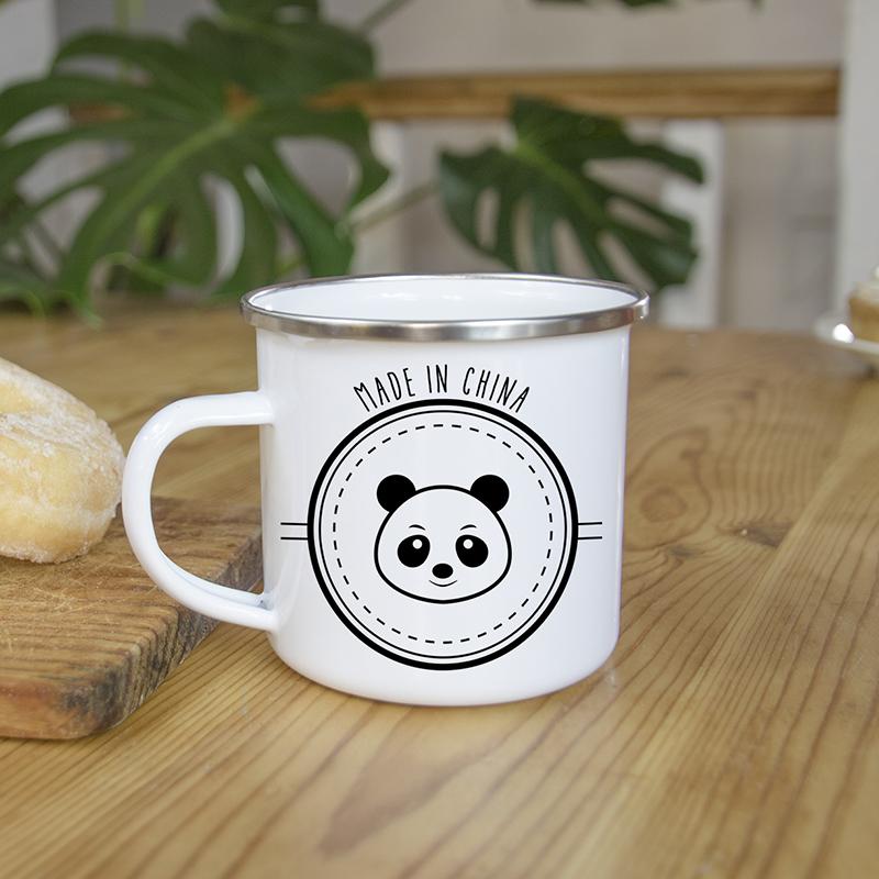 Mug en métal émaillé avec un panda, sur une table en bois